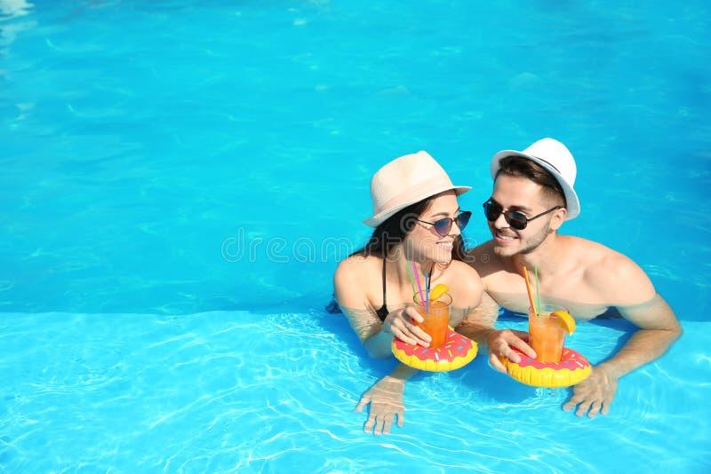 Barnpar med uppfriskande coctailar i simbassäng royaltyfri bild