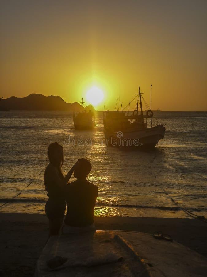 Barnpar och solnedgångstrand arkivbild