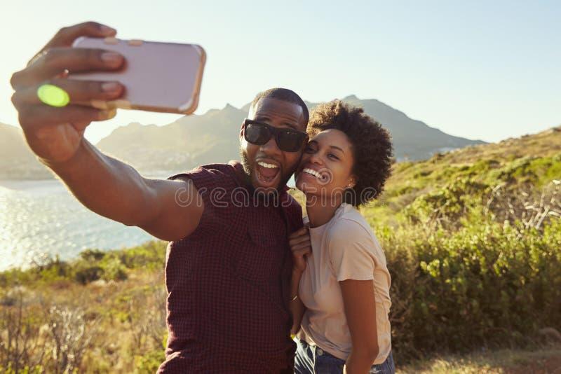 Barnpar poserar för ferie Selfie på Clifftop fotografering för bildbyråer