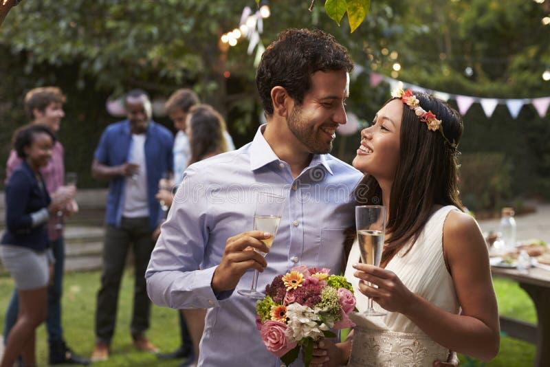 Barnpar som firar bröllop med partiet i trädgård arkivfoto