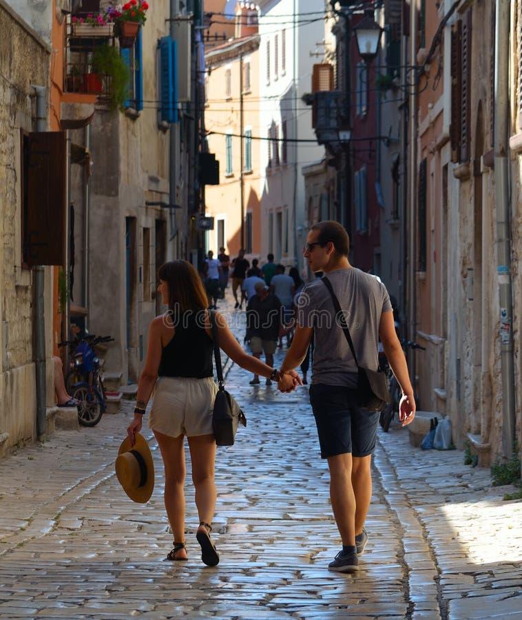 Barnpar som går handen - in - hand till och med gatorna av den gamla stadRovinj Istria Kroatien arkivfoton
