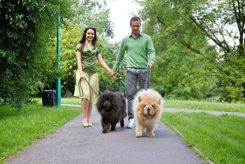 Barnpar som går med älsklings- hundkapplöpning arkivbild