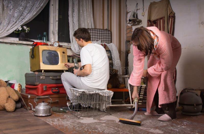 Barnpar som gör ren ett smutsigt rum royaltyfri bild