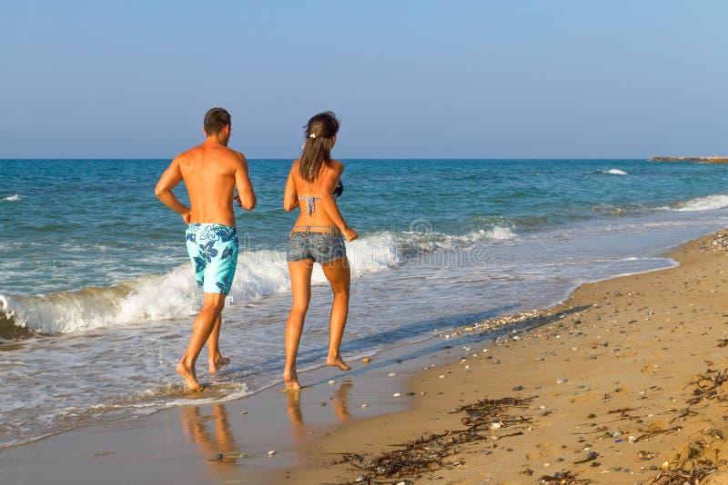 Barnpar som joggar på stranden royaltyfri bild