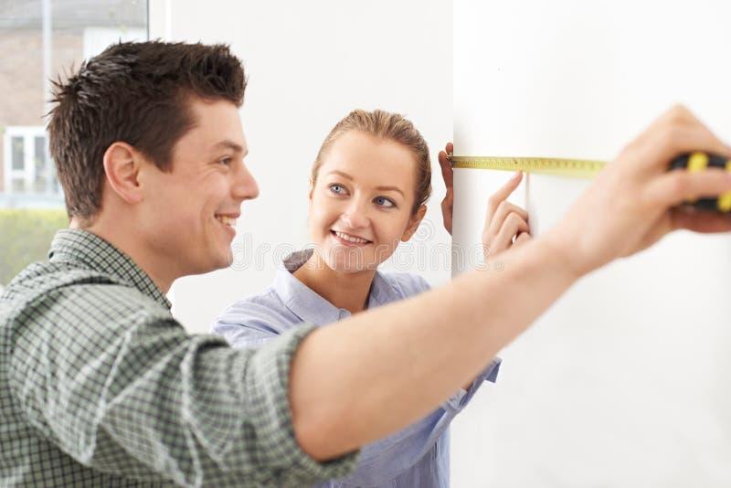 Barnpar som mäter väggen i nytt hem arkivfoton