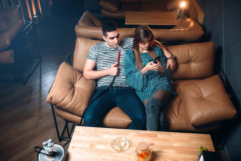 Barnpar som röker vattenpipan på lädersoffan royaltyfri fotografi