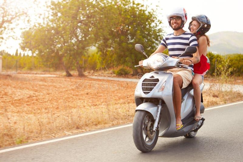 Barnpar som rider den motoriska sparkcykeln längs landsvägen royaltyfri fotografi