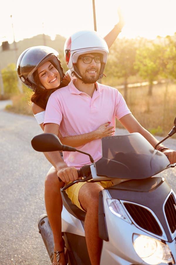 Barnpar som rider den motoriska sparkcykeln längs landsvägen royaltyfria bilder
