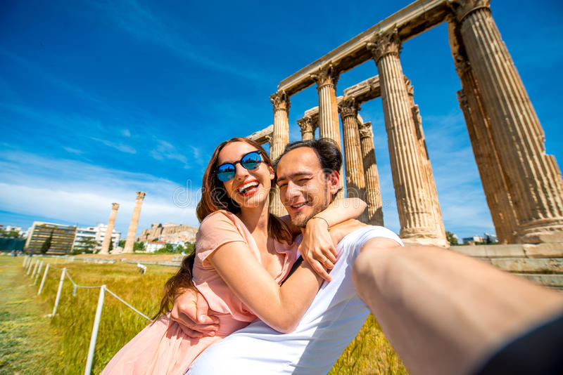 Barnpar som tar selfiebilden med den Zeus templet på bakgrund i akropol arkivfoton