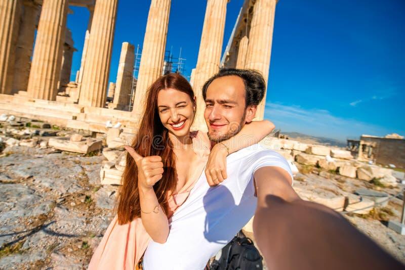 Barnpar som tar selfiebilden med Parthenontemplet på bakgrund i akropol royaltyfria bilder