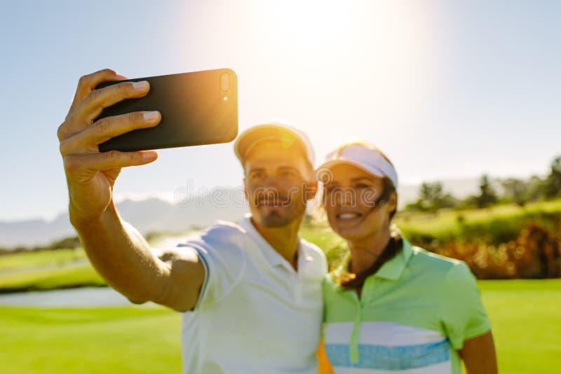 Barnpar som tar självståenden på golfbanan royaltyfria bilder