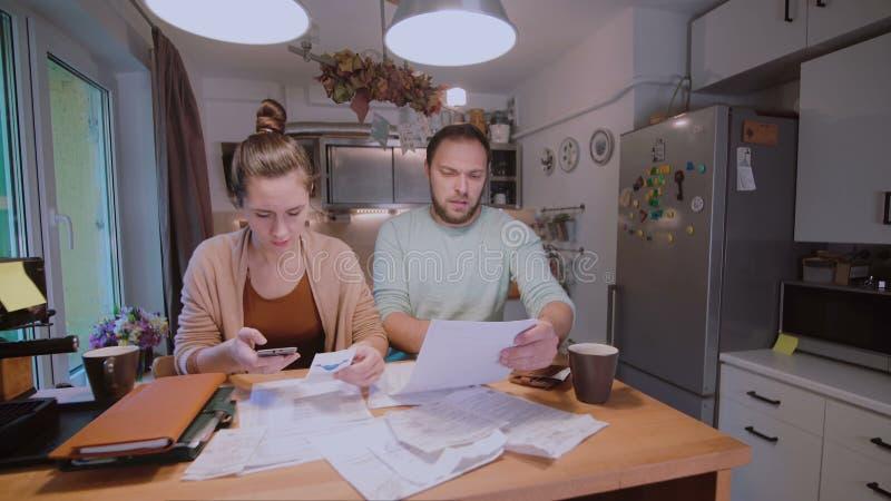 Barnpar som tillsammans beräknar deras hemhjälpbudget i köket, försök till säkra pengar och att ha spänningar