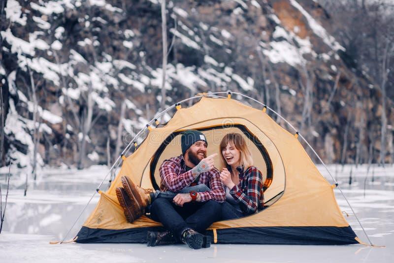 Barnparet sitter och skrattar i tält under vintervandring royaltyfri bild