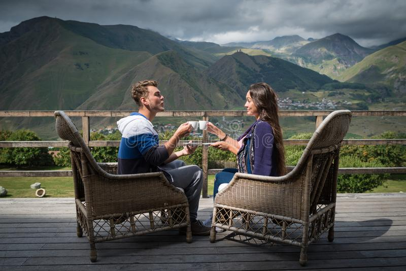 Barnparet sitter tillsammans på terrassen med koppar kaffe i morgonen royaltyfria bilder