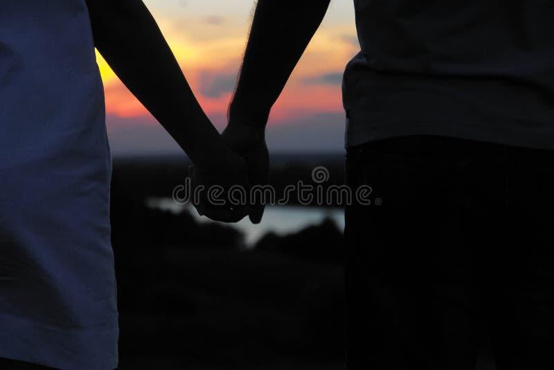 Barnparkontur mot solnedgånghimmel kvinnor för romantisk solnedgång för aftonmän väntande royaltyfria foton