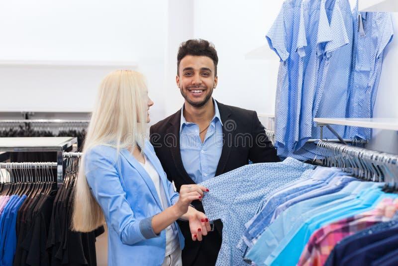 Barnparmode shoppar, den lyckliga le mannen och kvinnakunder som väljer shopping för formella kläder för kläder royaltyfri foto