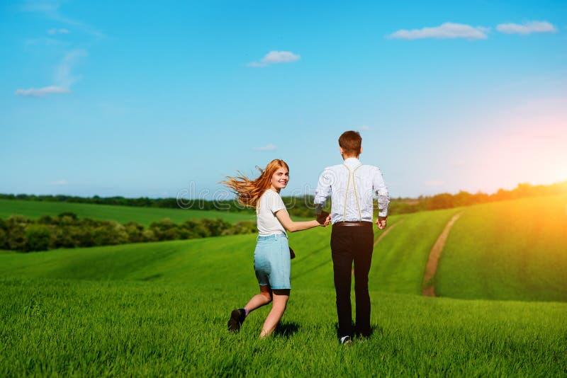 Barnparspring längs ett grönt fält på en älskvärd solig dag arkivbilder