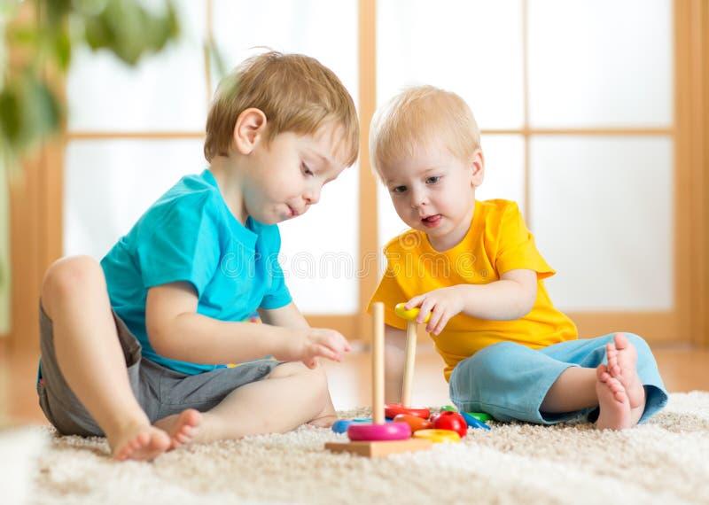 Barnpojkar med leksaker i lekrum arkivfoton