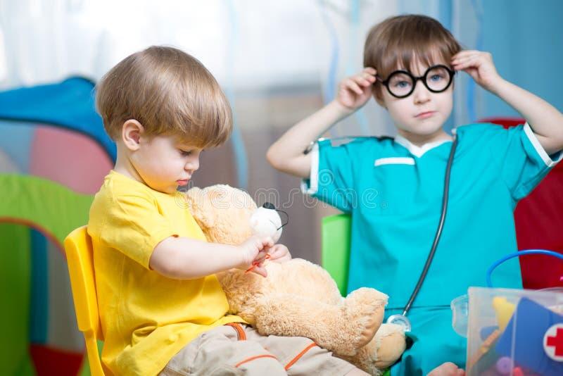 Barnpojkar som spelar doktorn och inomhus kurerar den flotta leksaken royaltyfri foto