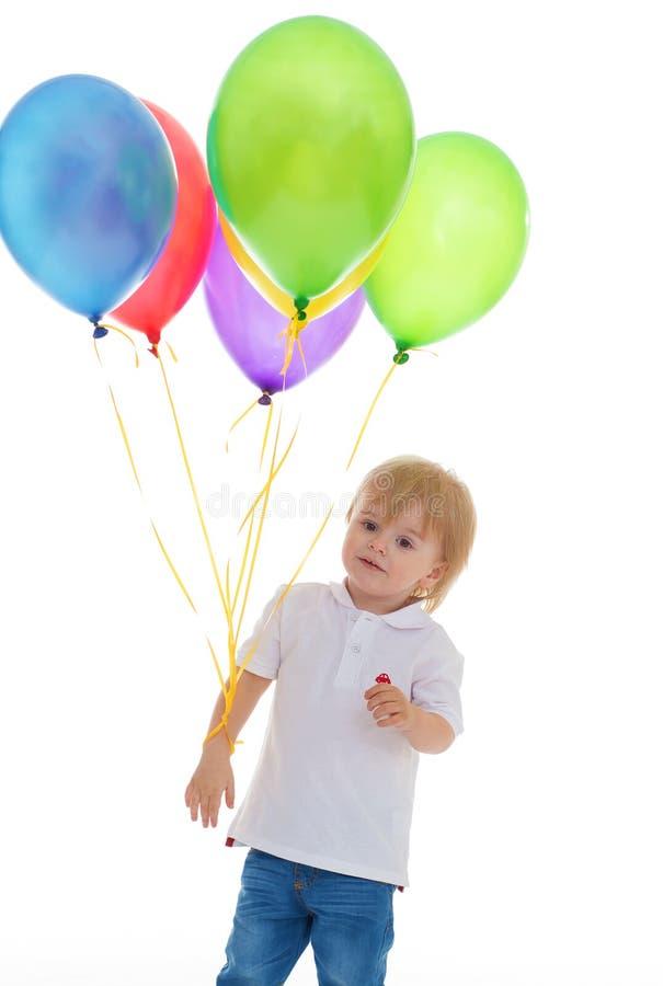 Barnpojke med gruppen av färgglade ballonger arkivbild