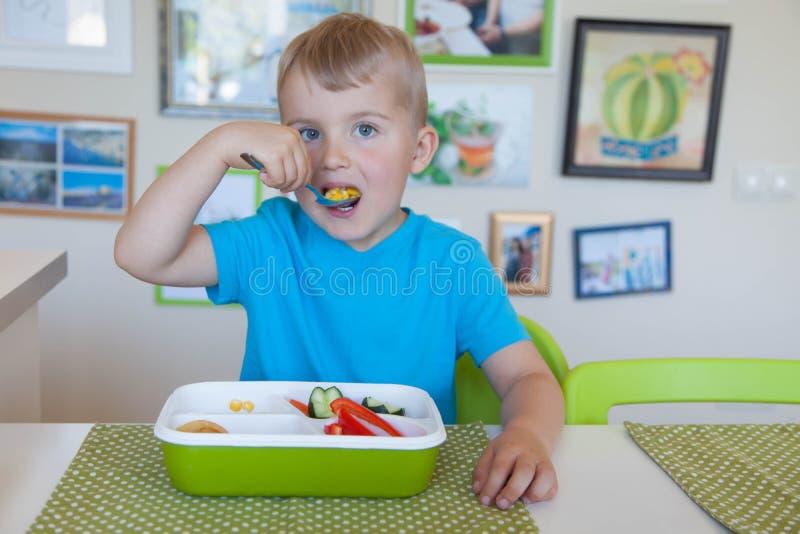 Barnpojke som äter sallad för ny grönsak arkivfoton