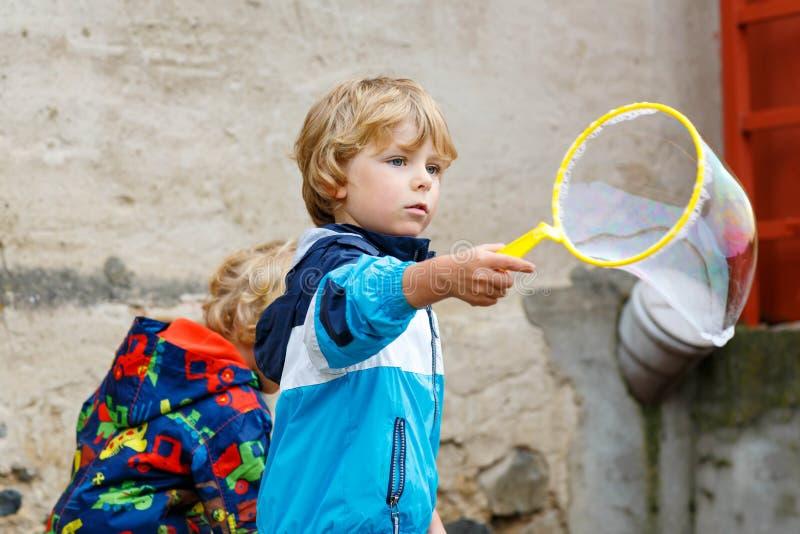 Barnpojke som blåser utomhus- såpbubblor royaltyfria foton