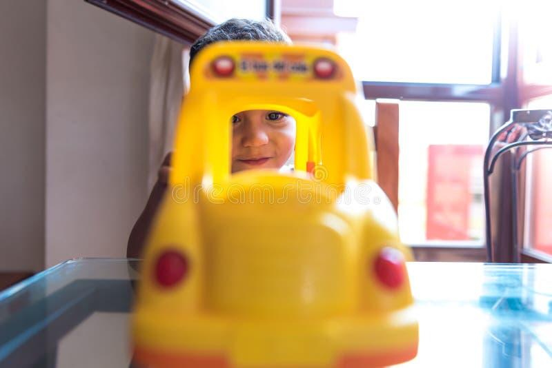 Barnpojke som spelar med en skolbussleksak inomhus royaltyfri foto