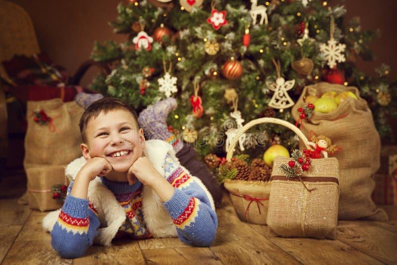 Barnpojkejulgran, lycklig unge som drömmer den närvarande gåvan för Xmas royaltyfri bild