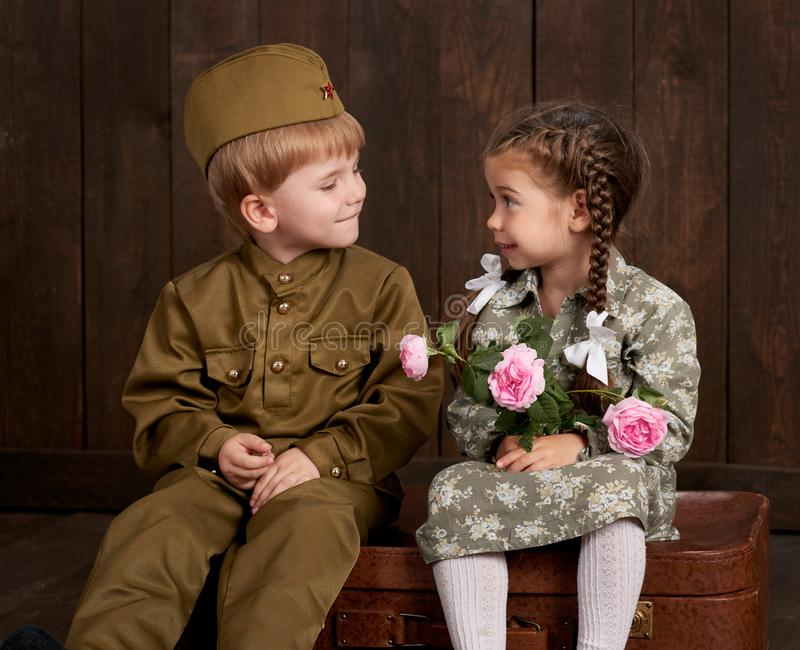 Barnpojken kläs som soldat i retro militära likformig och flicka i rosa färgklänningsammanträde på den gamla resväskan, mörk wood fotografering för bildbyråer