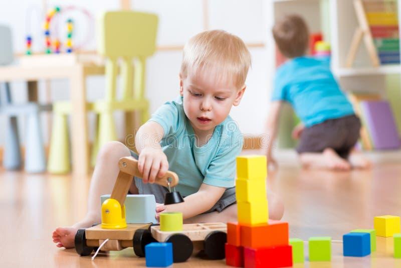 Barnpojken spelar med byggnadskvarter och bilsammanträde på golvet i dagis royaltyfri fotografi