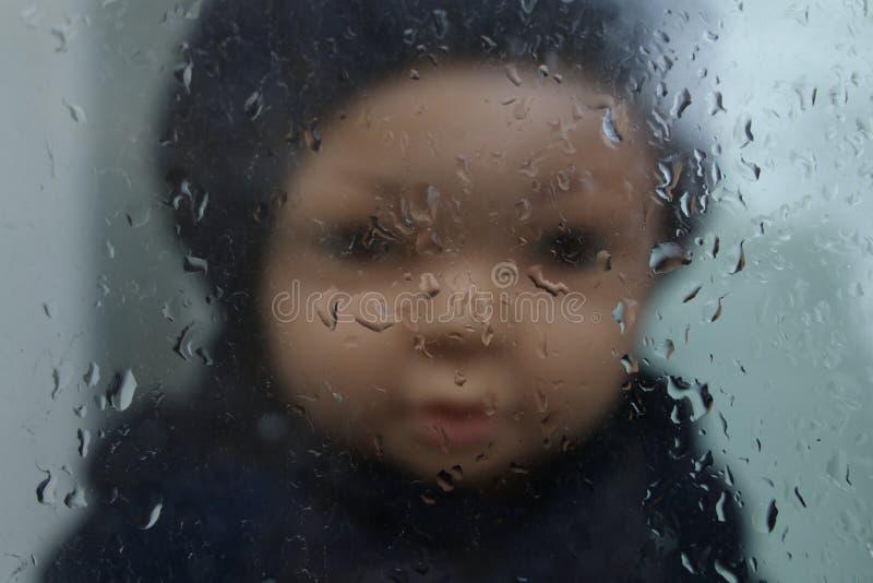 Barns docka i en svart hatt i ut-av-fokusen, bak exponeringsglaset arkivfoton