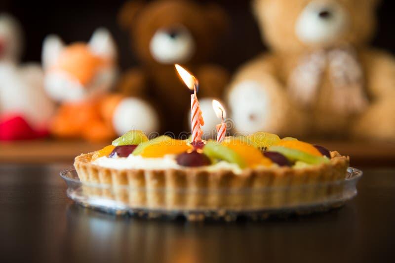 Barns födelsedagkaka med stearinljus, mjuk leksaker som bakgrund arkivbild