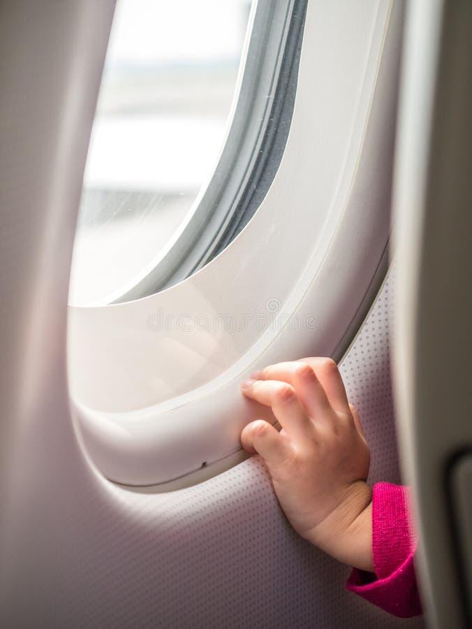 Barns fönster för flygplan för hand rörande arkivfoton