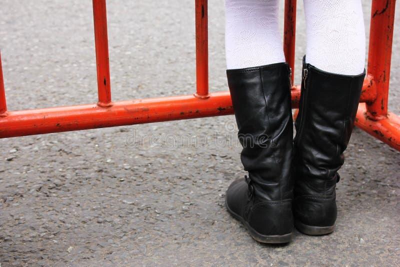 Barns fot är på asfalten framme av ett metallstaket Fot- trafik förbjudas arkivfoto