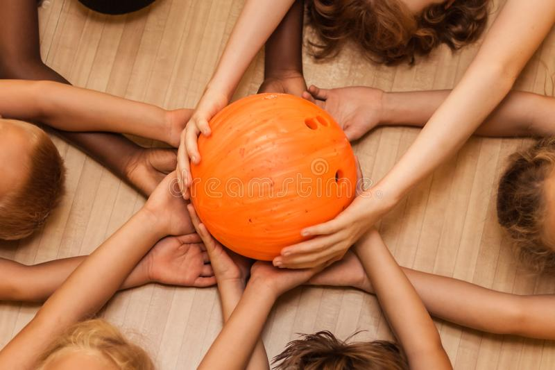 Barns händer av olika nationaliteter med en bowlingklot arkivbild