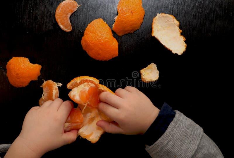 Barns händer borstar mandarinen på en svart bakgrund Barnet når för en skiva av mandarinen arkivbilder