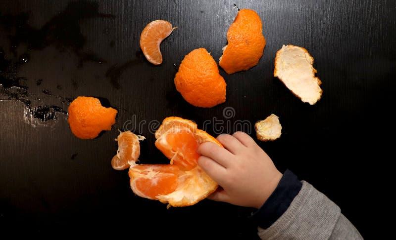 Barns händer borstar mandarinen på en svart bakgrund Barnet når för en skiva av mandarinen arkivfoto
