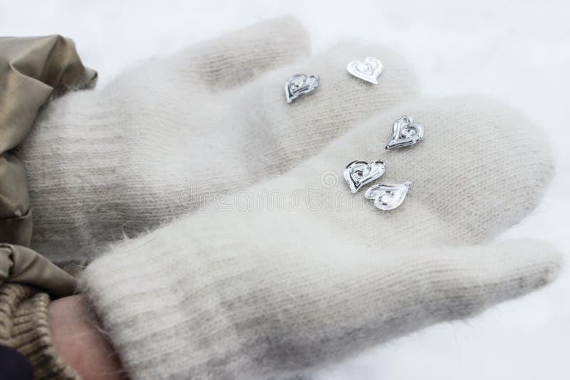 Barns händer i vinterhandskar rymmer hjärtor royaltyfri foto