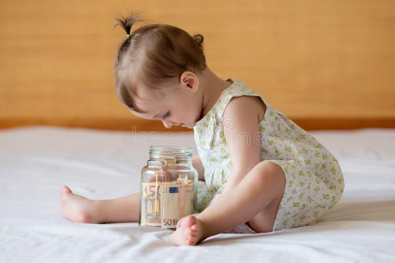 Barns händer med pengar i den glass kruset royaltyfria foton