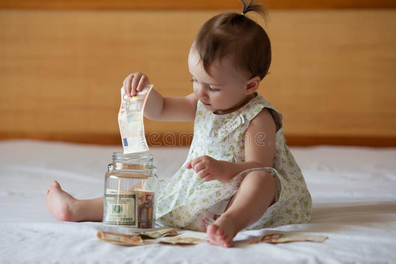 Barns händer med pengar i den glass kruset arkivfoto
