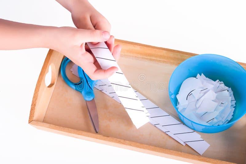 Barns händer rymmer ett trämagasin med montessorimaterial för en kurs Blå sax, bunke, ark för att klippa isolate arkivbilder