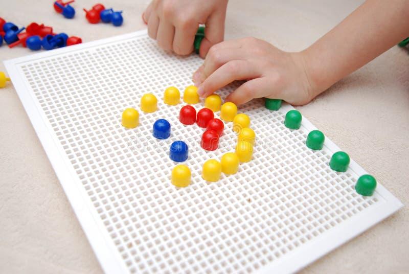 Barns händer som spelar med den mozaic idérika leken, slut upp, barndom, lek, utbildning som lär, utveckling arkivfoton