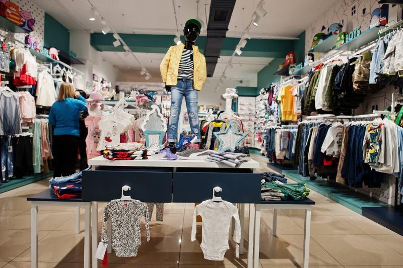 Barns hänger ljusa kläder på skärmen i behandla som ett barn det bekläda lagret med skyltdockan royaltyfria bilder