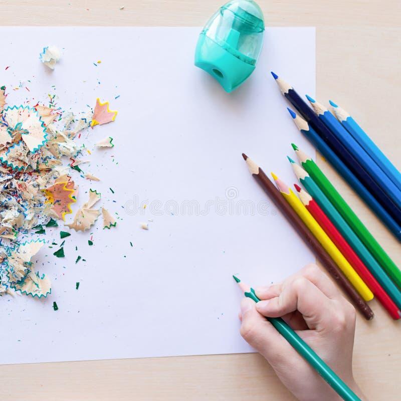 Barns hand drar med det vita arket för kulöra blyertspennor av papper Skolabegrepp eller kreativitet Fyrkantigt ramkopieringsutry royaltyfri foto