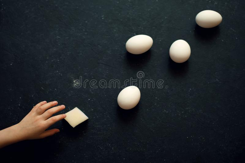 Barns hand når för äggen arkivfoto