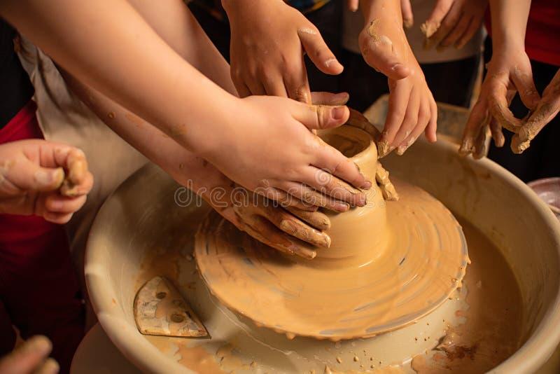 Barns handarbete med lera p? en special maskin Produkter fr?n lera royaltyfri bild