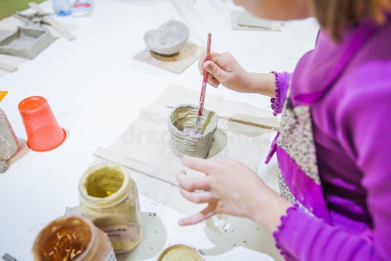 Barns handmålning med borste själv-gjorda leraobjekt arkivfoton