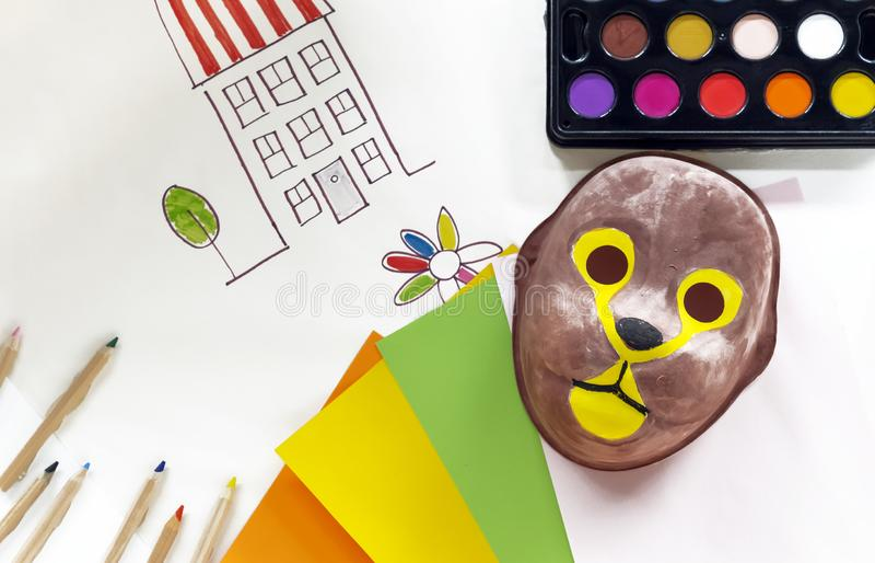 Barns karnevalmaskering som målas med målarfärger Begreppet av att färga maskeringar royaltyfria foton