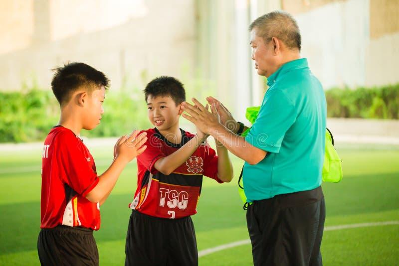 Barns lärande fotboll med föräldrar och lagledare arkivbilder