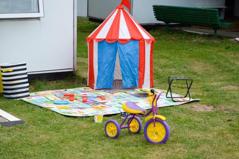 Barns lekplats i borggården av huset på gräsgräsmattan med ett tält, en tältleksaktrehjuling royaltyfria foton